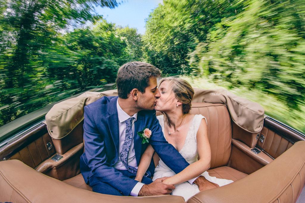 Photographie de La Corde au Coeur, photographe de mariage en Belgique. Portrait de couple dans lima voiture avec cérémonie à L'église. Vallée de la Molignée